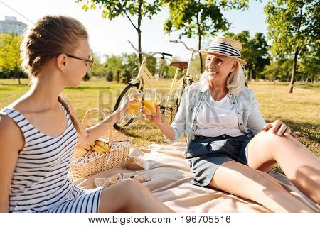Cheers. Delighted smilign senior woman having a picnic with her pretty granddaughter and drinking orange juice while spending time together