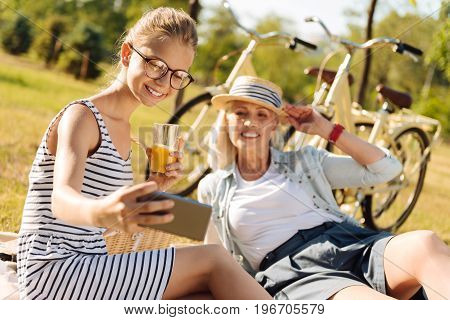 Full of positive emotions. Delighted smiling girl making selfies and resting in the park while having a picnic with her loving grandmother