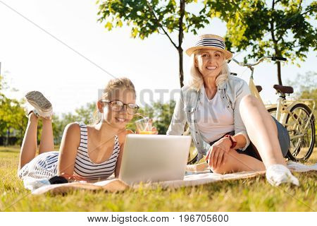 Always connected. Delighted positive girl using her laptop and resting on the blanket while having a picnic with her grandmother outdoors
