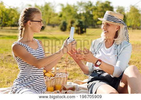 It is your turn. Positive charming teenager girl sitting on the blanket with her grandmother and giving her the headphones while enjoying the picnic