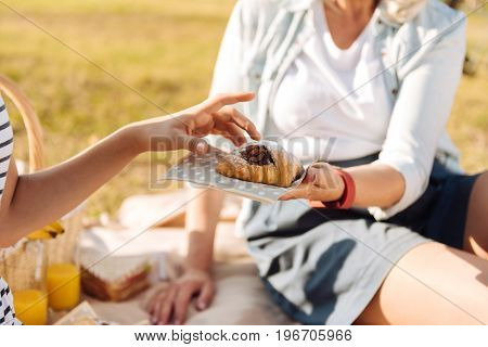 Help yourself. Close up of a croissant in hands of a pleasant senior woman giving it her little granddaughter while sitting on the blanket and enjoying the picnic