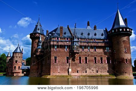 Medieval Castle De Haar from side of Moat against Blue Sky Outdoors. Utrecht Netherlands