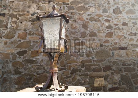 Antique lantern on the background of the old stone wall