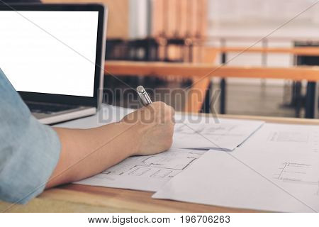 Image of engineer or architectural project Close up of hand architects engineering working on blueprint with engineering equipment tool Construction concept.