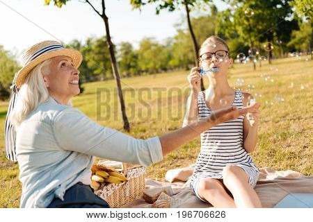 Happy childhood. Cheerful smiling loving senior woman sitting on the blanket with her granddaughter while she is blowing soap bubbles