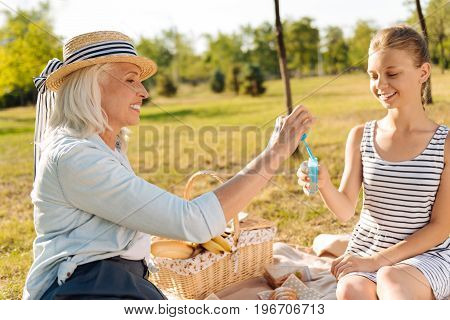 Remember your childhood. Cheerful delighted senior woman going to blow soap bubbles and resting outdoors with her granddaughter on a picnic