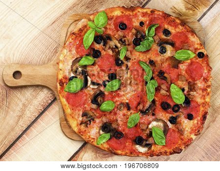 Homemade Pepperoni Pizza with Mushrooms Black Olives Ham and Basil on Wooden Cutting Board on Wooden background. Top View