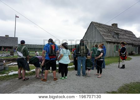 MACKINAW CITY, MICHIGAN / UNITED STATES - JUNE 18, 2017: Visitors observe archaeologists at work, as a costumed interpreter stands by with a musket, in Fort Michilimackinac, in the Colonial Michilimackinac State Park.