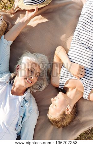 Joy and happiness. Cheerful smiling senior woman lying on the blanket and having a picnic with her granddaughter while resting in the park together