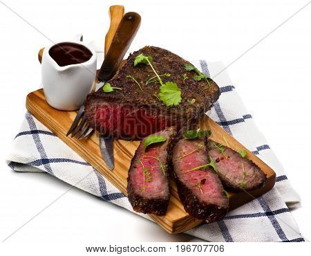 Delicious Roast Beef Medium Rare Sliced on Wooden Cutting Board with Tomato Sauce Fork and Table Knife on Checkered Napkin closeup on White background