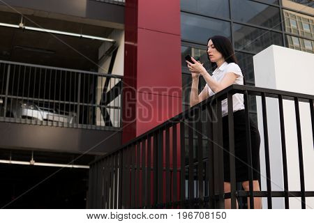 Successful business woman using smart phone in the city
