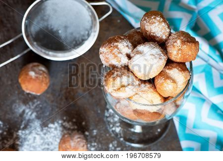 Homemade small donuts with powdered sugar in the glass on brown marble background