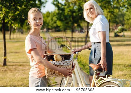 Enjoy every day. Cheerful young girl holding picnic basket and standing near a bicycle while going to have a picnic with her grandmother
