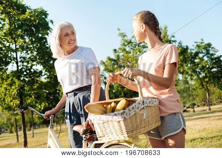Nice time together. Positive senior woman talking with her pretty granddaughter while standing near bicycle in the park and going to have a picnic