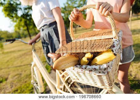 Join us. Close up of picnic basket in hands of a young girl holding it and standing near her bicycle while going to have a picnic with her grandmother