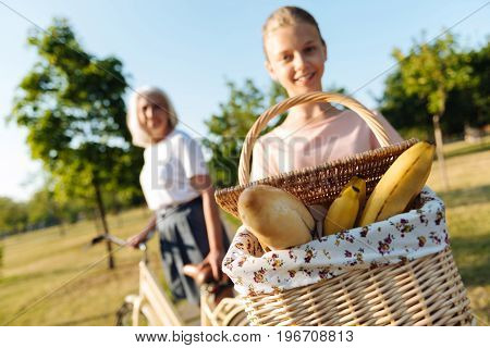 Only fresh food. Close up of basket with fresh meal in hands of a pleasant girl holding it while going to have a picnic with her grandmother