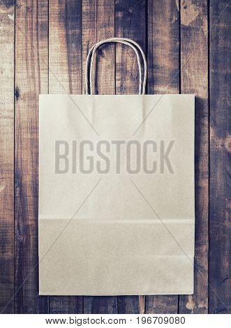Photo of recycled paper shopping bag on vintage wood table background. paper shopping bag. Toned image.