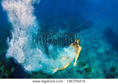Happy girl dive deep down underwater in coral reef sea pool. Travel lifestyle, summer beach water sports adventure and swimming lessons on family holiday with kids