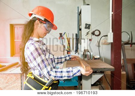 Asian pretty female carpenter using Electric Sander for wood.