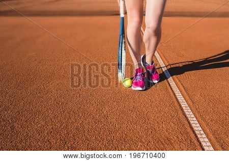 Closeup photo of female legs with tennis racket