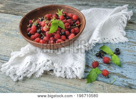 Berries of raspberries and currants in a plate on a wooden table