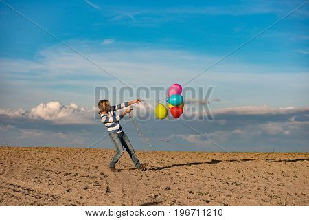 Birthday girl with colourful balloons outdoors