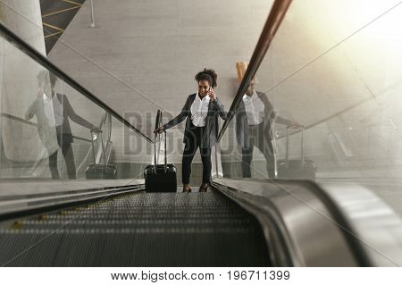 Businesswoman using escalator at airport terminal and holding smartphone