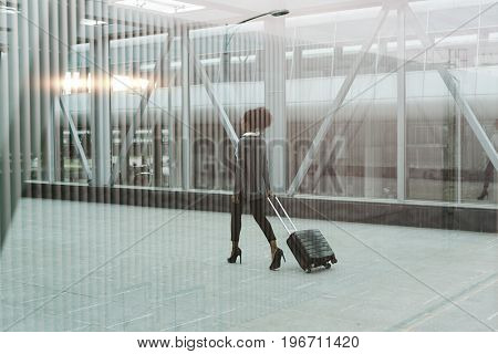Modern businesswoman pulling her suitcase, back view shot through window