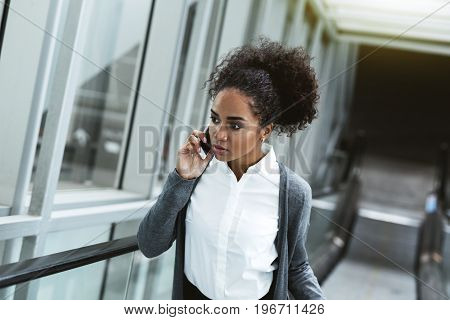 Woman making phone call while lifting up on escalator