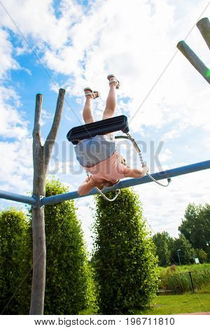 The child swings on a swing. The child is flying very high upside down. Happy childhood flight happiness concept.