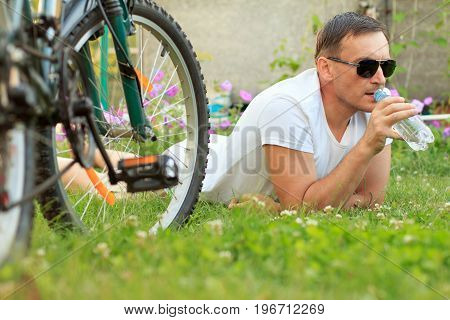 Close up view of man lying on green grass and drinking water from a bottle. Picture of male in white T-shirt and sunglasses with bottle of water lying on green grass with road bicycle beside him in the garden. Selective focus on man. Healthy active lifest