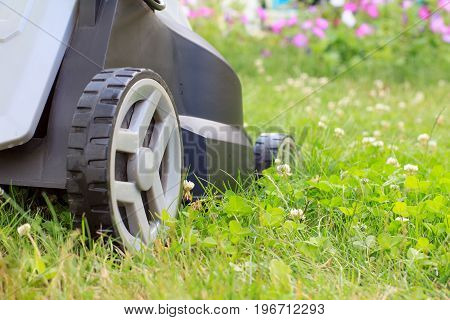 Close up view of lawn mower on green grass in the garden. Mower grass equipment. Mowing gardener care work tool. Shallow depth of field