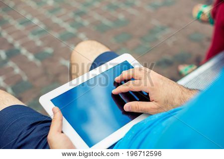 Man sitting on a bench and using a digital tablet. Men's hands closeup