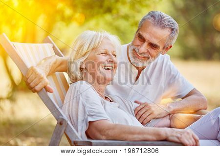 Senior couple on a summer holiday sitting on a deck chair