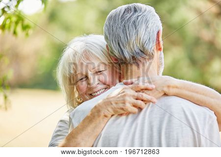 Happy old lady hugging a man in the nature in summer