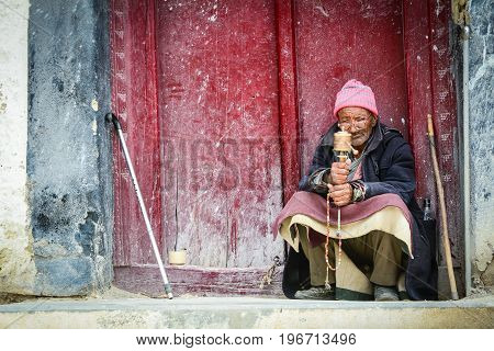 Tibetan Man Sitting And Praying At House
