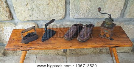 Wo Old Rusty Antique Iron With Wooden Handle, Hand Coffee Grinder And Leather Clogs On Old Wooden Be