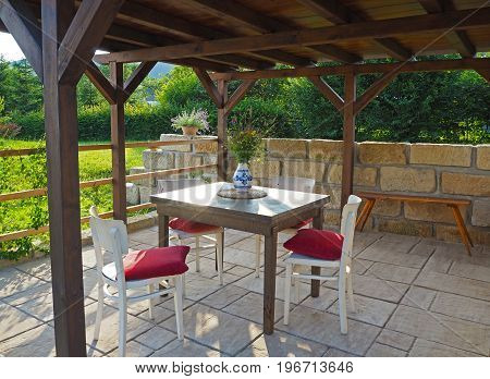 Brown Tiber Wooden Gazebo - Pergola With Table And Chairs With Red Pillows With Sandstone Wall And F