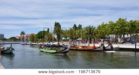 AVEIRO PORTUGAL - JUNE 10 2017: Traditional boats moliceiro on main city canal. Aveiro known as Venice of Portugal also known for its production of salt which is used for fertilizer in the area
