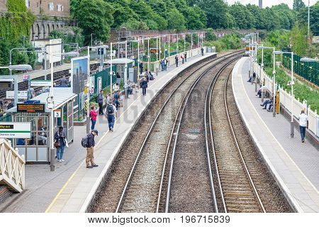 West Brompton Overground Station Platforms, With Commuters Waiting On Platforms