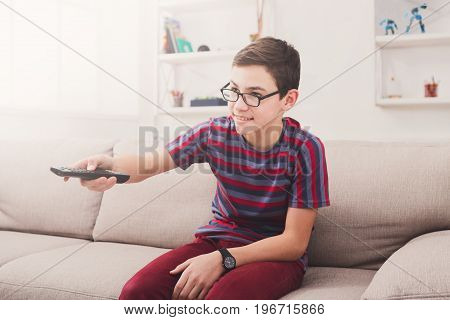 Teenager boy watching television, pointing with remote conroller while sitting on couch in living room at home