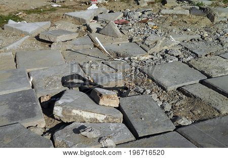 Devastated soil and broken paving stones in the suburban area