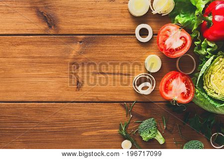 Cooking healthy food background. Sliced leek, fresh organic vegetables on wood with copy space. Natural food with copy space.