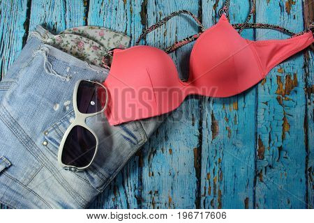 Summer collage - jeans shorts, bikini bra and sunglasses/ Jeans shorts, bikini bra and sunglasses on wooden blue background.