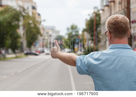 Man Standing On The City Street And Hailing A Taxi