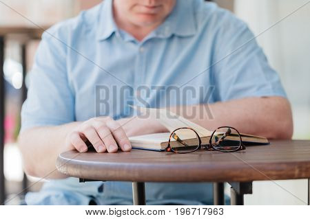 concentrated man reading book in city cafe