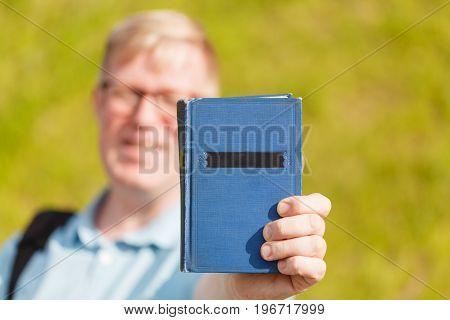 Book In Man's Hands In Gesture Of Giving