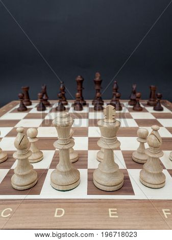 Chessboard with wooden figures placed opposite each other