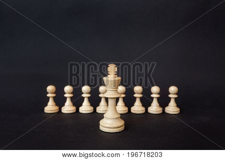 Chess pieces on a black background. The white king stands on the background of pawns.