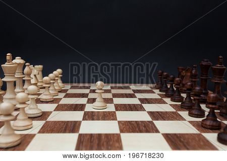 First move by white pawn on the center of board. Chess board on a black background